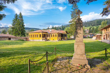 Monument with cross and characteristic yellow house on green lawn in koprivshtitsa
