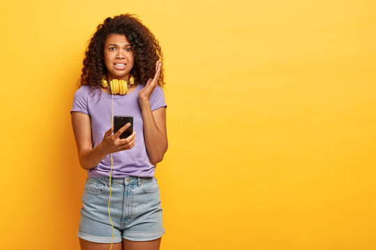 Displeased dark skinned curly woman listens disgusting voice message in headphones, holds modern smartphone, wears purple t shirt and denim shorts, stands against yellow studio wall, copy space
