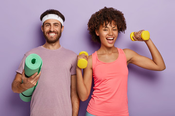 Improve your muscles. Sporty woman trains with dumbbells, has cheerful look, her husband stands near, holds rolled up fitness mat, enjoy athletic training together, isolated on purple background