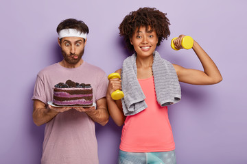 Surprised young Afro man stares at delicious cake, wears white headband, feels temptation, happy woman works on biceps, raises weights, leads sporty lifestyle, stand against purple background.