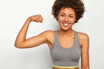 Positive smiling mixed race young woman raises muscular arm, shows biceps, has powerful look, smiles happily, dressed in sport bra, isolated over white background, says look how strong I am.