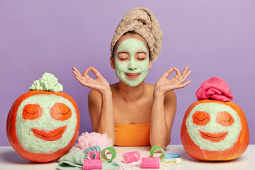 Relaxed woman gets beauty treatments, meditates indoor, poses at table with cosmetic accessories and autumn crops, applies facial masks on pumpkins, has clean healthy skin, isolated over purple wall