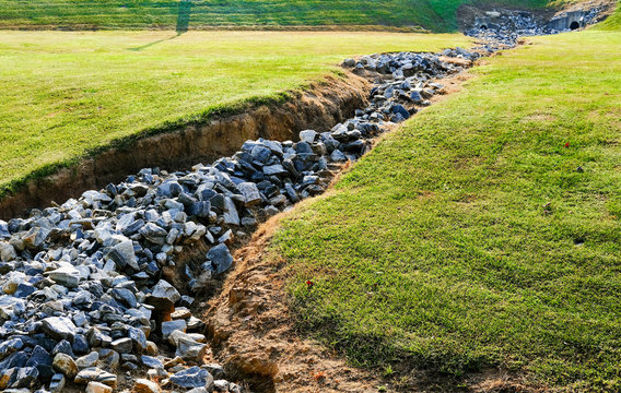 Large Granite Rocks in Drainage Ditch in Green Field