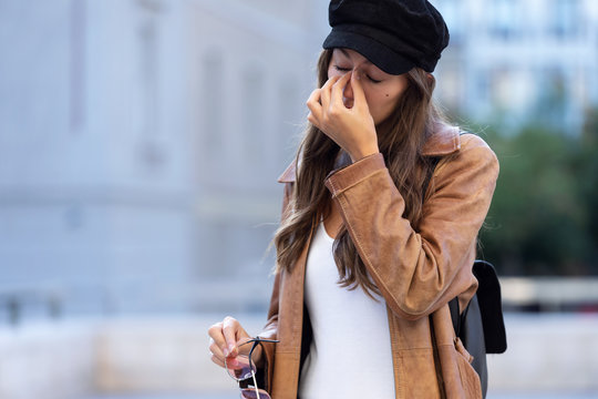 Painful young woman suffering headache while standing in the street.