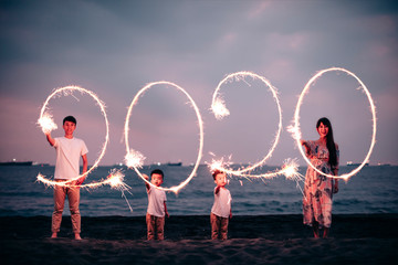 happy asian family celebrating new year 2020 on the beach