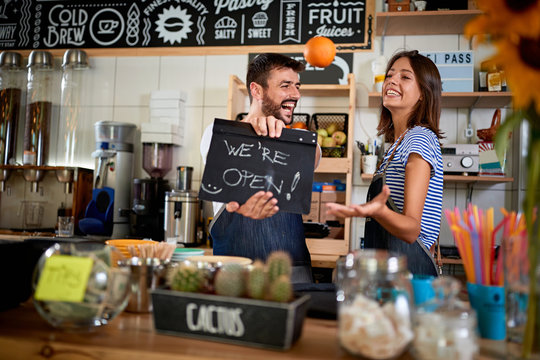 Business owner holding Open Sign. Man and woman  opening their store
