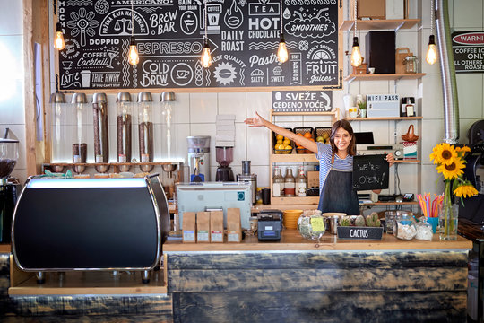 Coffee shop is open - woman at workplace at new open café.