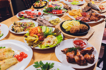 Dining table with a variety of snacks and salads. Salmon, olives, wine, vegetables, grilled fish toast. The concept of a family celebratory dinner. Thanksgiving, Christmas. top veiw.