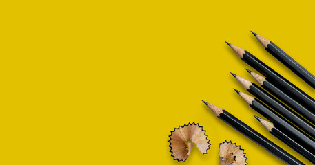 Black pencils placed on yellow paper background with copy space for your image or text.