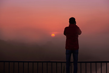Marron chocolat A silhouette of a man on a bridge over the river that photographs a sunrise on a foggy morning.