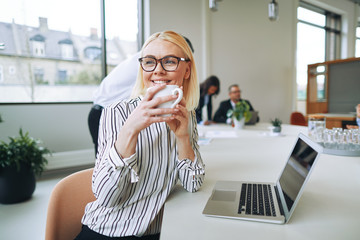 Smiling businesswoman enjoying a coffee while woring in an offic