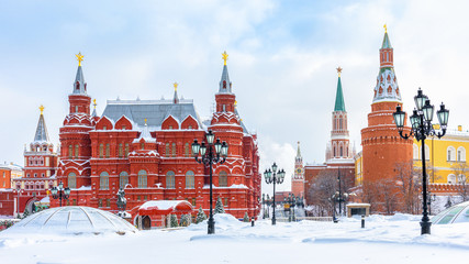 Fototapete - Moscow in winter, Russia. Manezhnaya Square overlooking Moscow Kremlin, top landmark of city. Panorama of Moscow center during snowfall. Scenery of old Moscow buildings under snow.