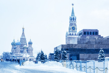 Fototapete - Moscow Red Square in winter, Russia. This place is a famous tourist attraction of Moscow. Cold winter view of St Basil Cathedral and Moscow Kremlin. Panorama of Moscow city center during snowfall.