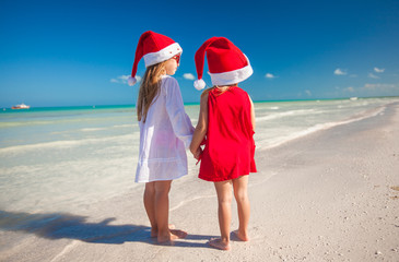 Little cute girlsin Christmas hats on the exotic beach