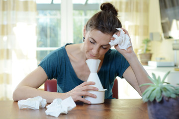 Woman has a bad cold and is trying therapy by inhaler