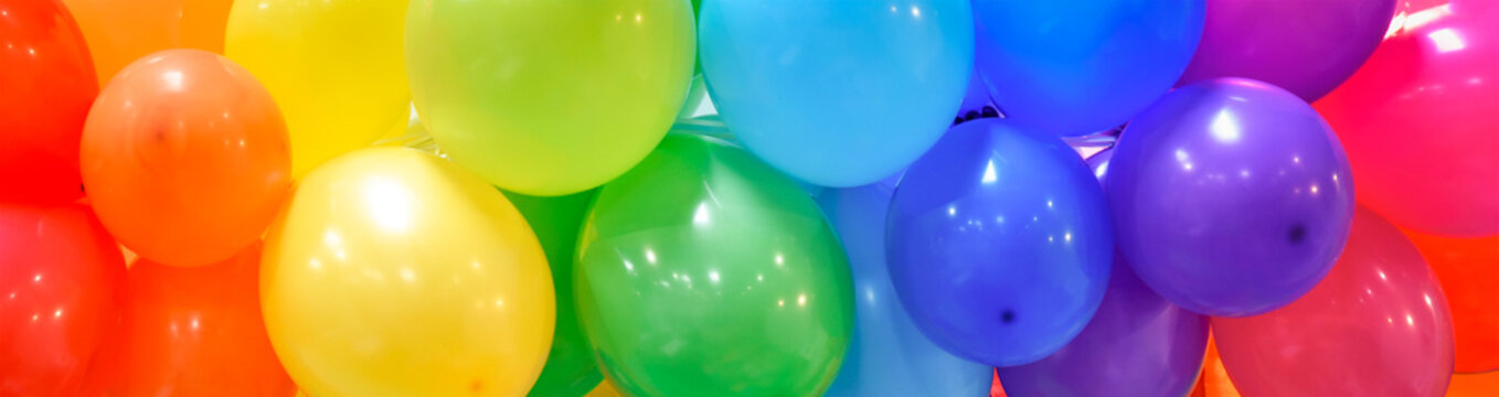 Wide celebration banner background with rainbow multicolored balloons.