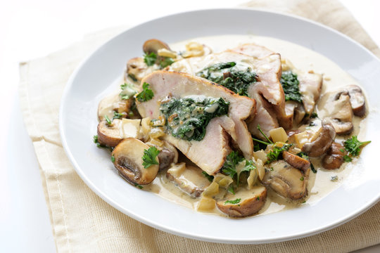 stuffed chicken breast fillet with spinach, mushrooms and a creamy gorgonzola sauce on a white plate