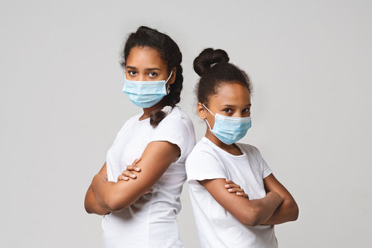 Two young sisters wearing medical masks, staying back to back