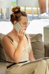 Travail à domicile - Jolie jeune femme téléphonant avec un smartphone durant son travail assise dans un patio sur un golf et appelant un client