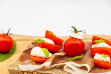 Sandwich italien sur une tranche de pain multi céréales avec une tranche de jambon rouge des tomates cerises billes de mozzarella et du basilic frais sur une assiette en bois -isolé fond blanc