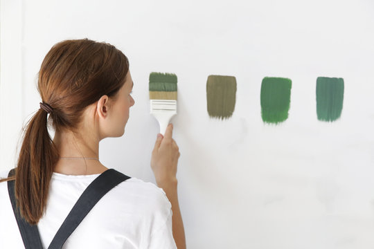 Woman is painting the wall with different color swatches. Process of choosing the right color for the wall, DIY home improvement concept.