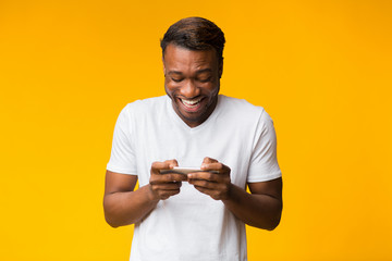 Excited Black Man Using Cellphone Playing Games, Studio Shot