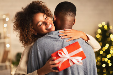 Thankful afro woman with christmas gift hugging husband at home