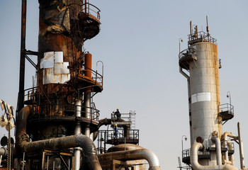 Employees work at the damaged site of Saudi Aramco oil facility in Abqaiq