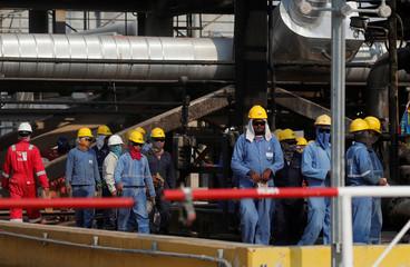 Workers walk at Saudi Aramco oil facility in Abqaiq