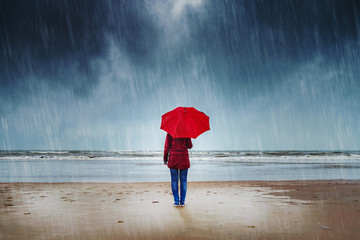 Lonely woman with red umbrella is standing in the rain watching the sea