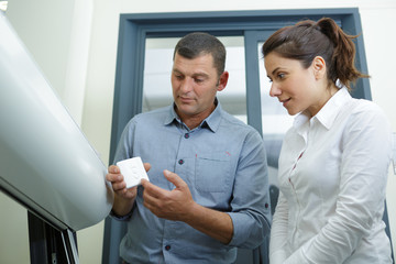 couple buying new heating water boiler in supermarket