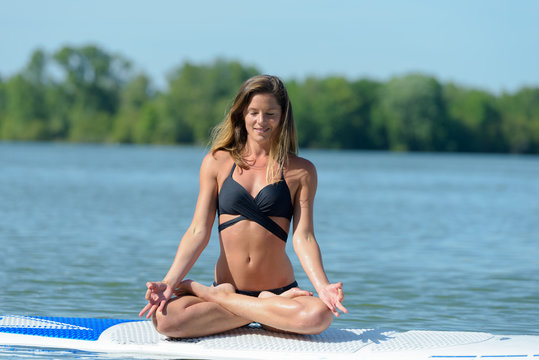 woman in the lotus position on a paddle board