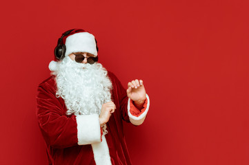 Cheerful Santa Claus in sunglasses dancing on a red background, listening to music in headphones and having fun at a party. Santa at christmas party. New Year concept. Copyspace