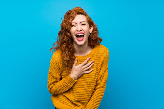 Redhead woman with yellow sweater smiling a lot