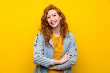 Redhead woman over isolated yellow background laughing