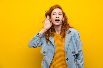 Redhead woman over isolated yellow background listening something