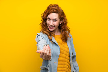 Redhead woman over isolated yellow background inviting to come