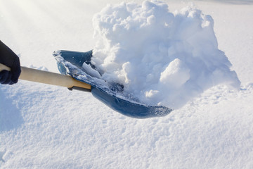 Man holding snow removing shovel with snow while cleaning backyard