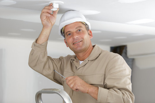 handsome male electrician changing the light bulb
