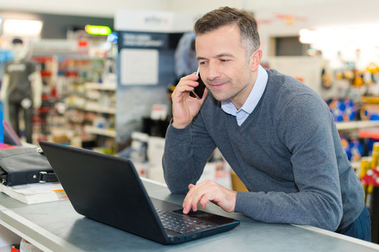salesman talking on smartphone while looking at laptop