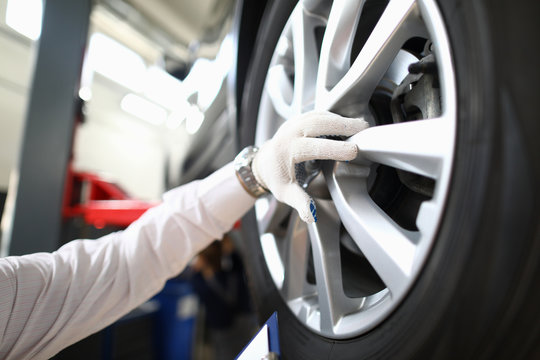 Focus on specialist male hand wearing white glove and inspecting titan discs of modern sporting automobile wheels. Machinery repairman and service station concept