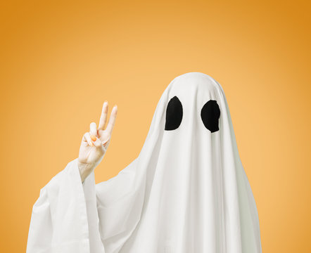 Halloween white ghost showing peace sign gesture on yellow background.