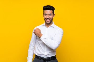 Young handsome man over isolated yellow background celebrating a victory Wall mural
