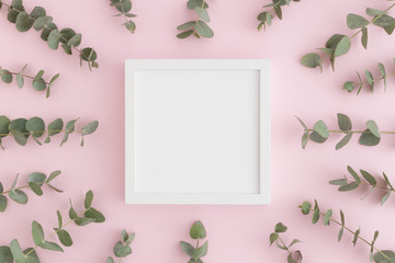 Top view of a white square frame mockup surrounded by branches of eucalyptus on a pink background.