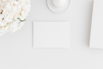 Top view of a white card mockup with workspace accessories and flowers on a white table.