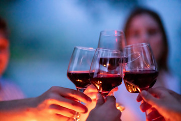 friends toasting red wine glass during french dinner party outdoor