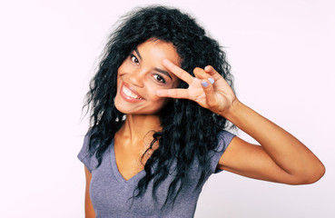 Cutie pie. Front portrait of a beautiful African American woman with long loose raven black hair looking at the camera, smiling broadly and showing V-sign near eyes with her left hand.