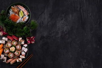 Foto op Aluminium Sushi bar Assorted sushi sashimi set with salmon, tuna and eel on dark slate background with decorations. Christmas or New Year background. Tree branch with gifts. Traditional japanese food