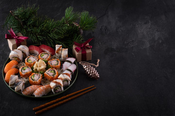 In de dag Sushi bar Assorted sushi sashimi set with salmon, tuna and eel on dark slate background with decorations. Christmas or New Year background. Tree branch with gifts. Traditional japanese food. Copy space for text