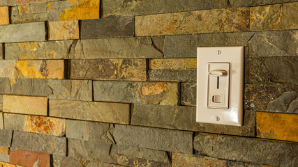 A light switch on a tiled stone wall